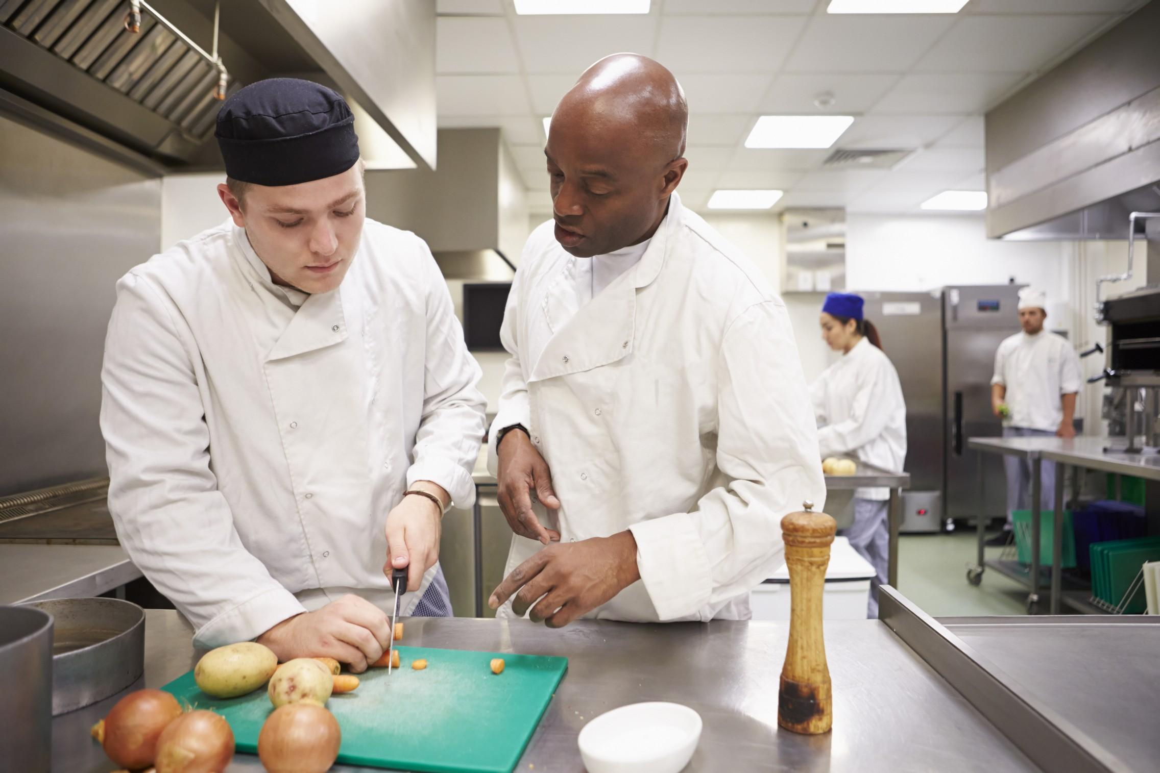 Chef ayuda a su equipo de cocina